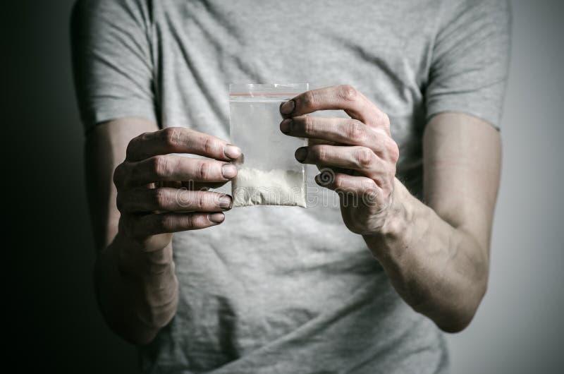 Бой против лекарств и темы наркомании: addict держать пакет кокаина в серой футболке на темной предпосылке стоковая фотография