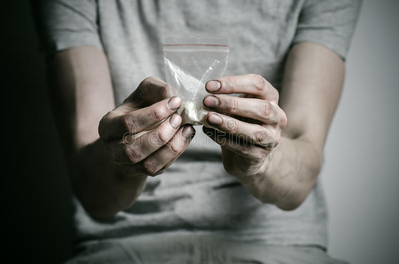 Бой против лекарств и темы наркомании: addict держать пакет кокаина в серой футболке на темной предпосылке в стоковая фотография
