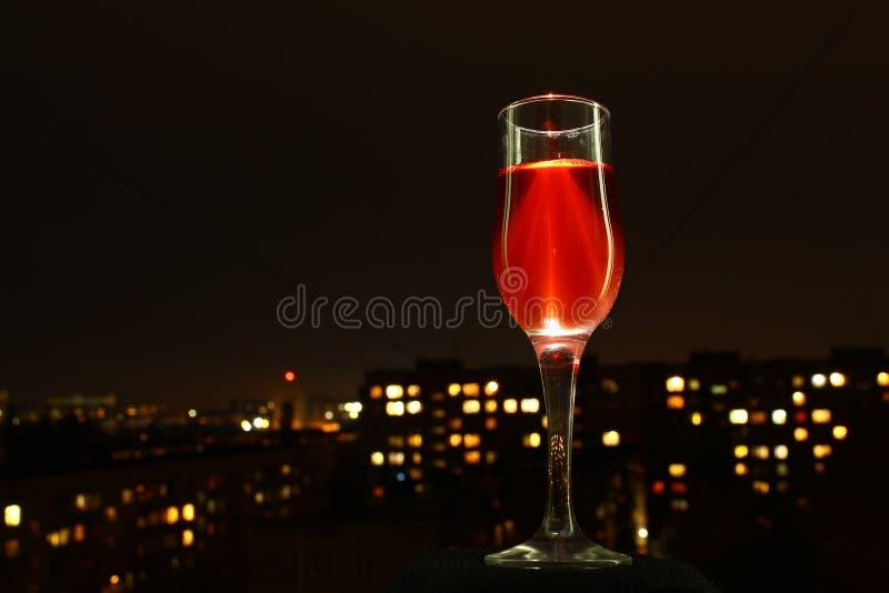 бокал вина на фоне города ночи стоковая фотография