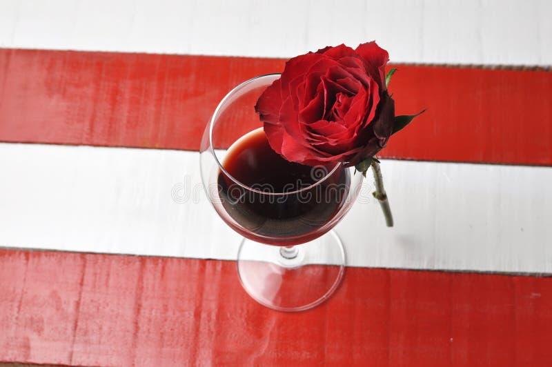 Бокал и красивая красная роза на белой красной предпосылке лепестки подняли стоковая фотография