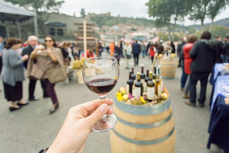 Бокал вина на пробуя зоне ежегодного фестиваля Tbilisoba города с толпой людей вокруг Страна Тбилиси, Georgia стоковые изображения rf