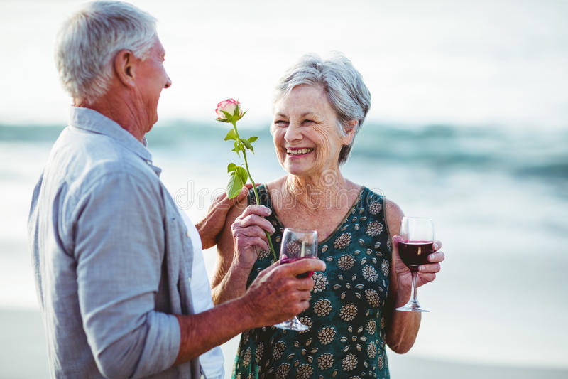Бокалы старшего удерживания пар розовые и красные стоковые изображения