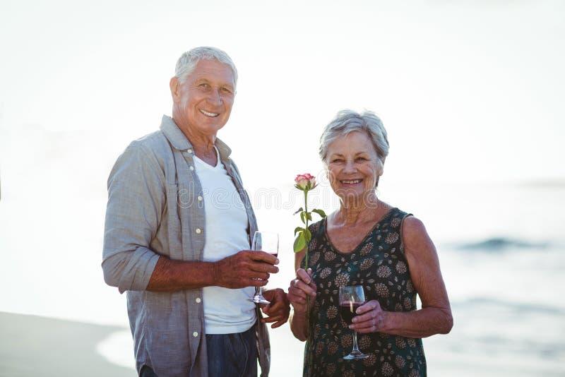 Бокалы старшего удерживания пар розовые и красные стоковые изображения rf