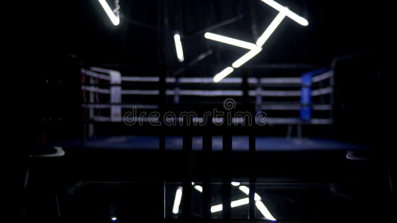 Боксерский ринг и 2 стуль с предпосылкой темноты таблицы Взгляд регулярн боксерского ринга окруженного синью ropes spotlit мимо стоковые изображения