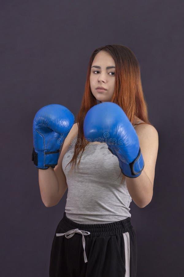 Боксер девушки женщин кладя в коробку стоит в перчатках бокса стоковые фотографии rf