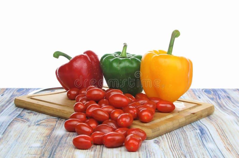 Болгарские перцы и томаты младенца на предпосылке белизны прерывая доски стоковая фотография
