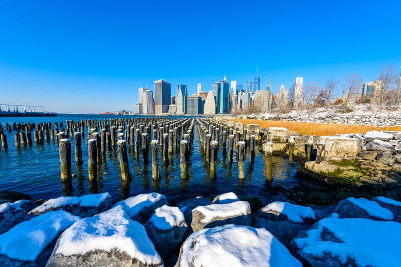 Более низкая панорама горизонта Манхэттена в снежном зимнем времени от берег реки берега реки парка Бруклинского моста, Нью-Йорка стоковые изображения rf