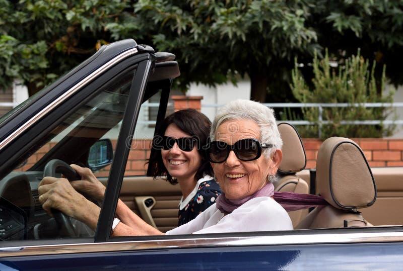Более старая женщина и молодая женщина управляя автомобилем с откидным верхом стоковые изображения