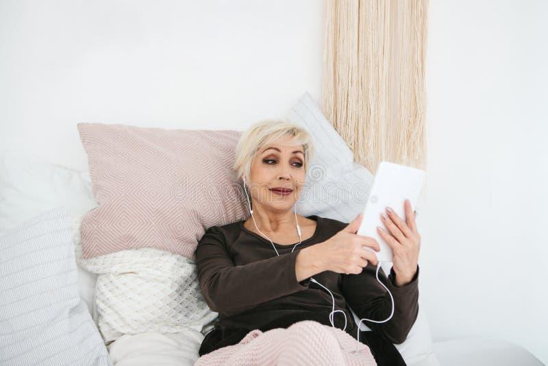 Более старая положительная женщина использует таблетку для того чтобы наблюдать видео, слушать к музыке и беседовать с друзьями н стоковое изображение