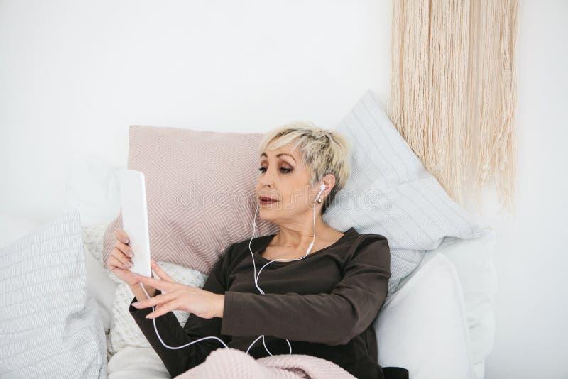 Более старая положительная женщина использует таблетку для того чтобы наблюдать видео, слушать к музыке и беседовать с друзьями н стоковые изображения