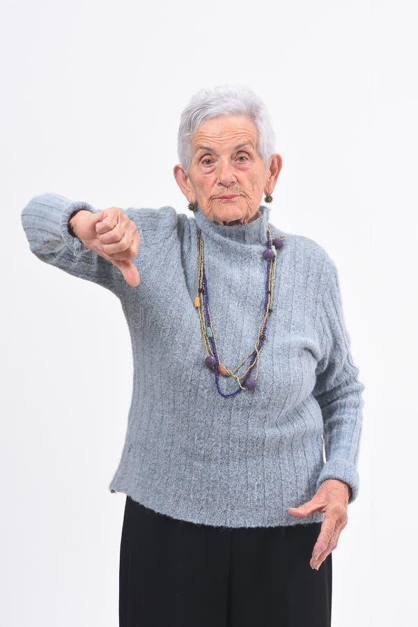 Более старые женщина держа ее большой палец руки вниз и серьезный на белой предпосылке стоковое фото