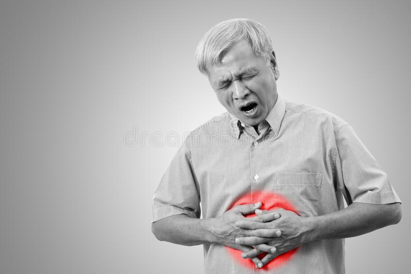 Более старый азиатский человек имеет концепцию боли боли в животе с изолированной предпосылкой стоковые изображения