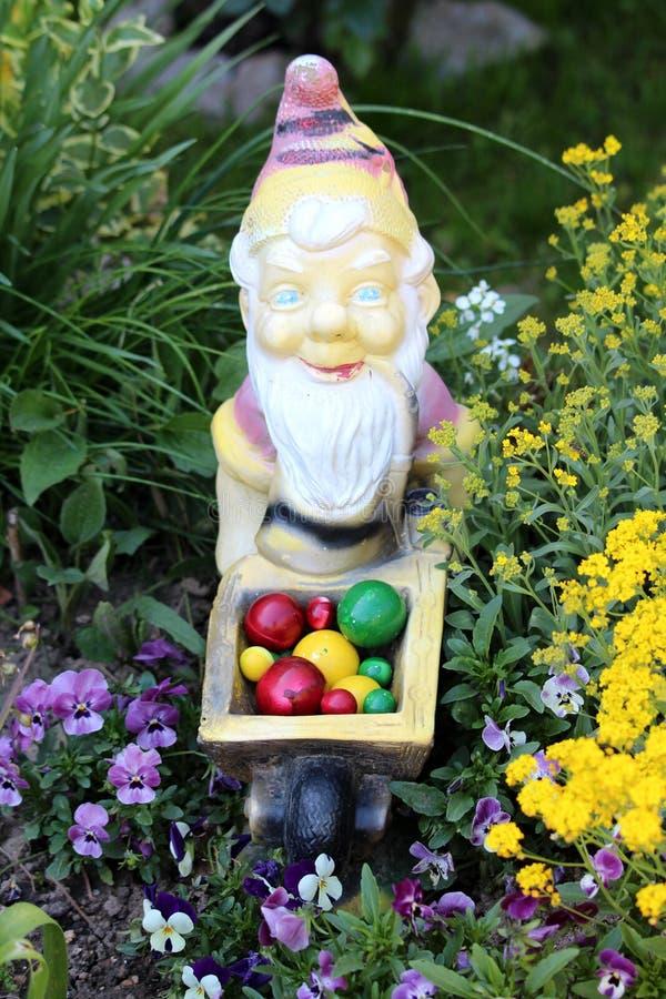 Более старый гном сада управляя красочными пасхальными яйцами в тележке конструкции тачки окруженной с заводами и цветками в мест стоковое фото