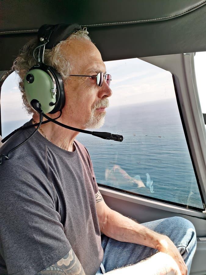 Более старый человек в вертолете, нося шлемофоне стоковое изображение rf