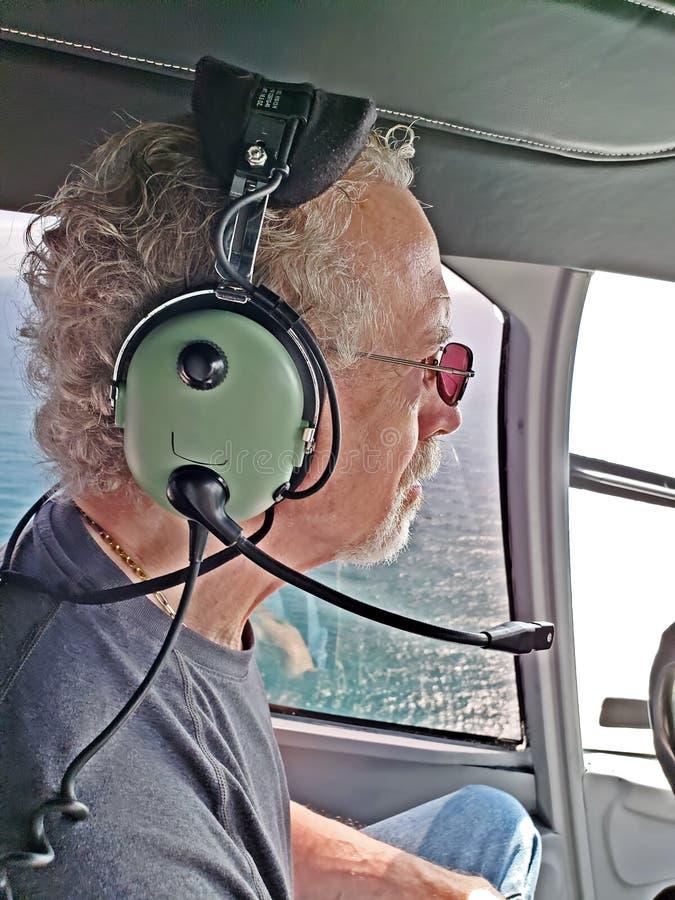 Более старый человек в вертолете, нося шлемофоне стоковое изображение