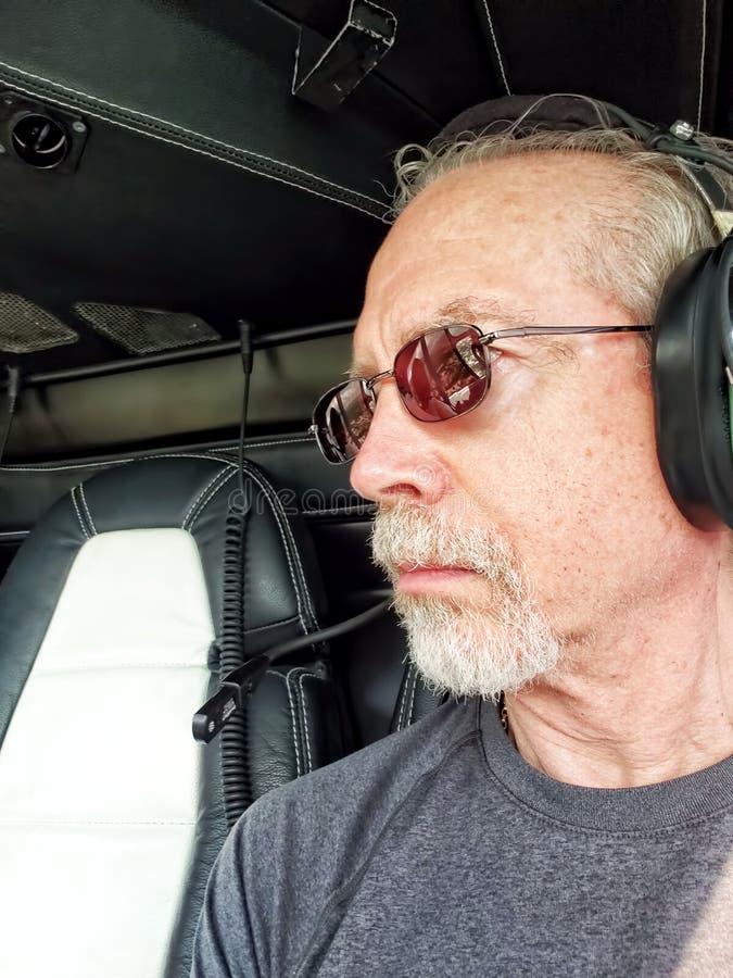 Более старый человек в вертолете, нося шлемофоне стоковое фото