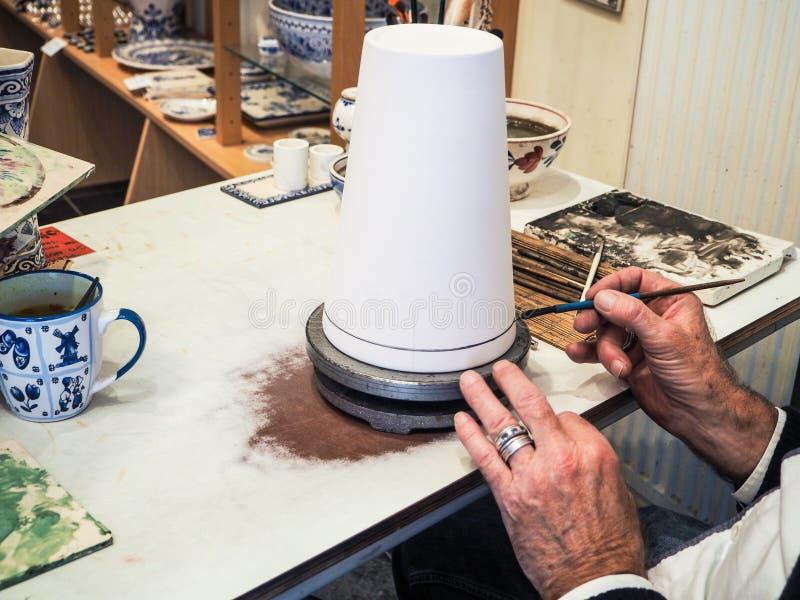 Более старый человек делая фарфор Делфта в его мастерской стоковое изображение