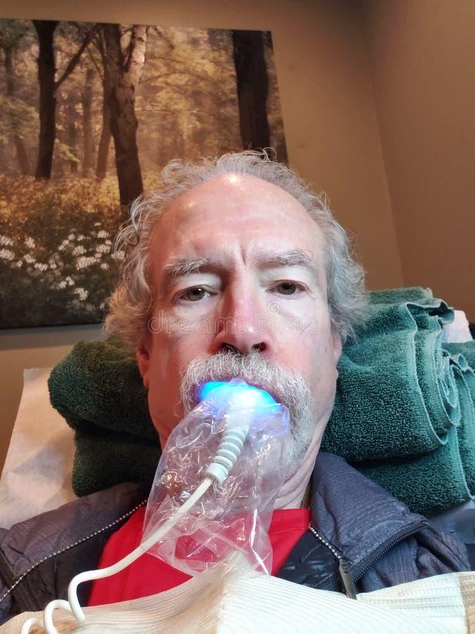 Более старый человек получая зубы забеленный стоковое изображение