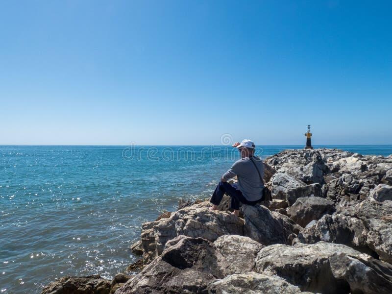Более старый человек сидя на камнях около моря, смотря на море стоковое фото