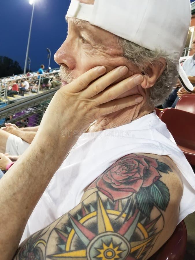 Более старый человек с goatee и пробуренной крышкой выражения нося белой на стоковые фотографии rf
