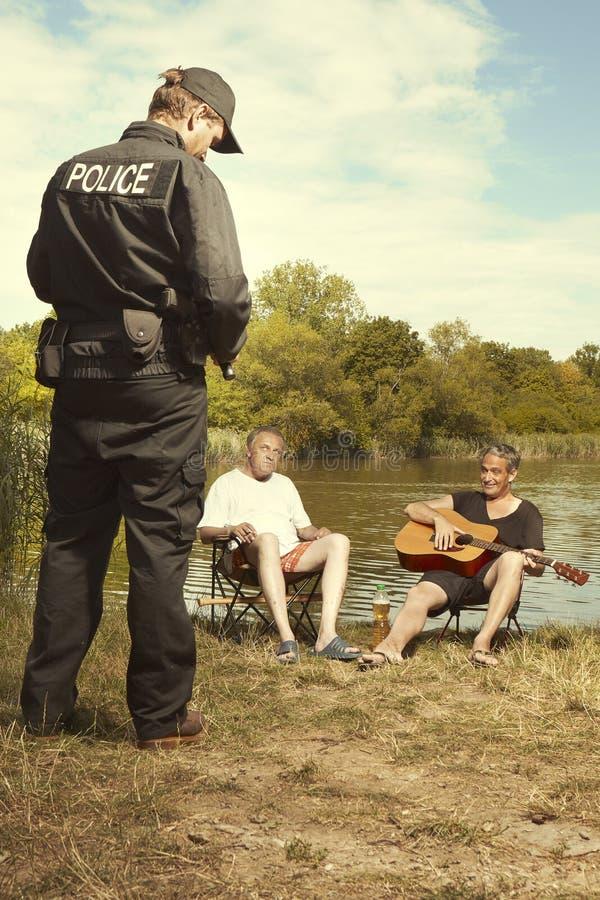 2 более старых люд говоря к человеку полиции озером лета стоковая фотография rf