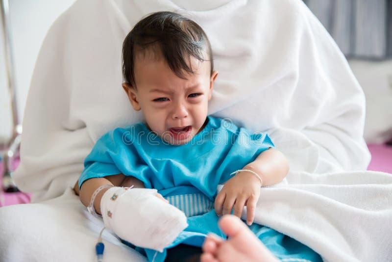Болезнь детей Маленький младенец прикрепляя внутривенную трубку в руку пациента в больничной койке Больной младенца и плакать на  стоковое изображение