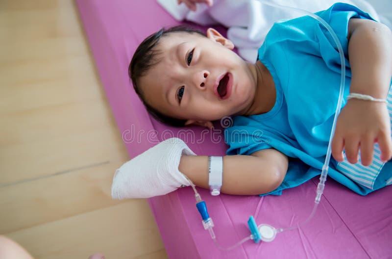 Болезнь детей Маленький младенец прикрепляя внутривенную трубку в руку пациента в больничной койке Больной младенца и плакать на  стоковое фото rf