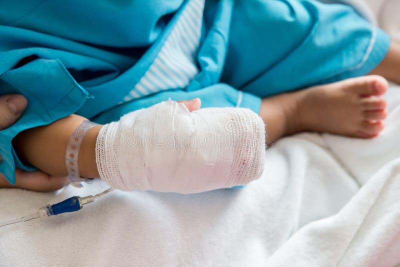 Болезнь детей Маленький младенец прикрепляя внутривенную трубку в руку пациента в больничной койке стоковые изображения rf