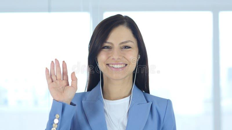 Болтовня женщины занятая онлайн видео-, развевая рука стоковое фото