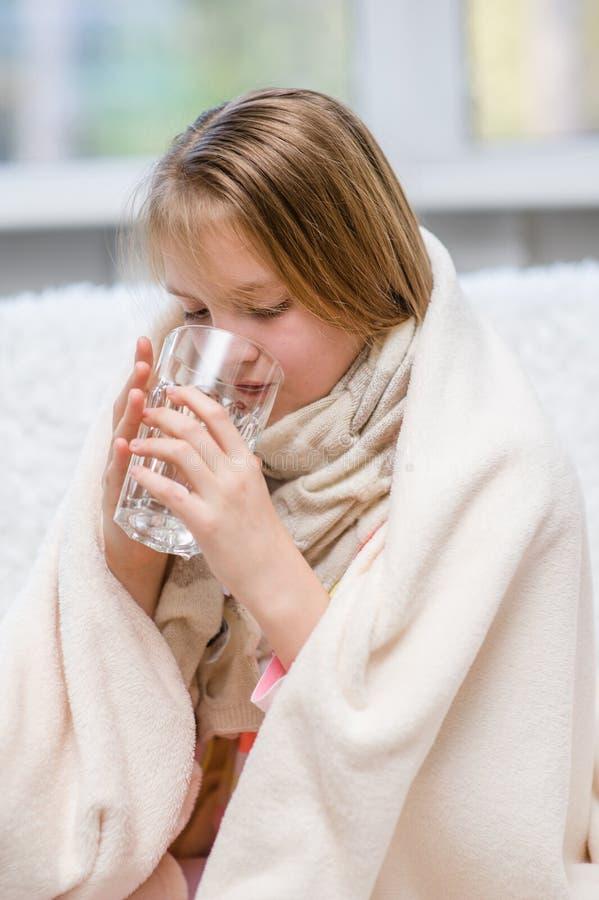 Больная девушка выпивает воду стоковое фото