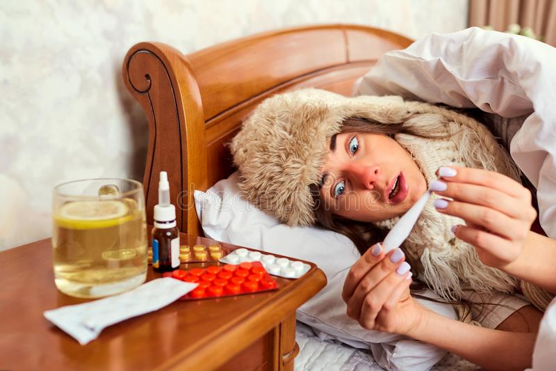 Больная девушка лежа вниз смотрящ термометр стоковое фото rf
