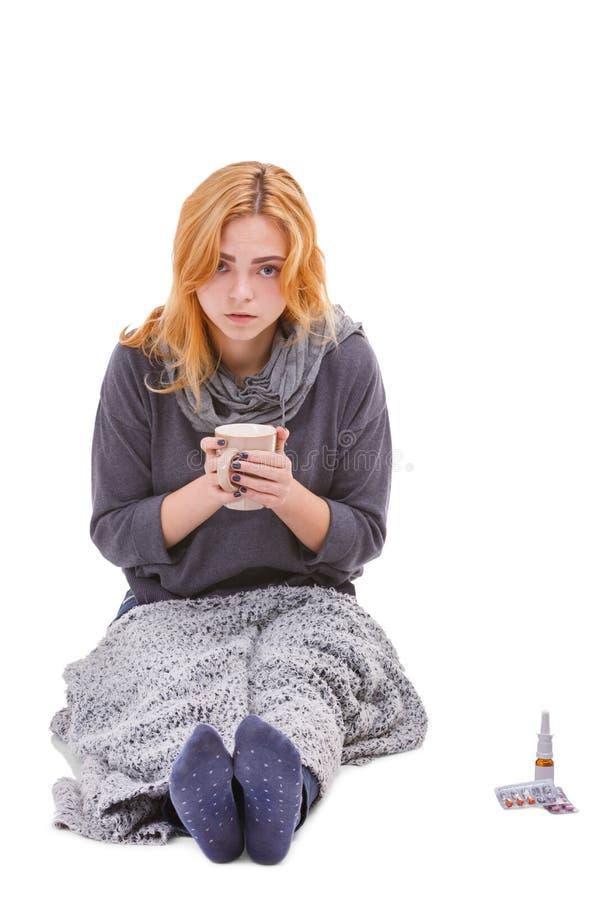 Больная девушка, обернутая в одеяле, сидит и выпивает что-то от чашки Изолировано на белизне стоковое изображение