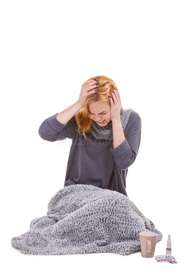 Больная девушка, обернутая в одеяле, сидит рядом с медицинами и демонстрировать головную боль изолировано стоковое фото