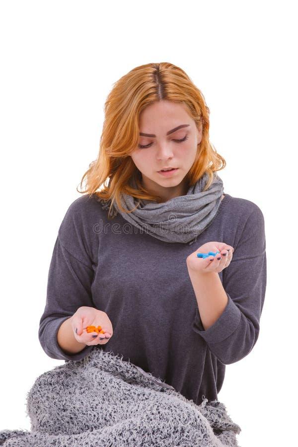 Больная девушка, предусматриванная в одеяле, держит различные пилюльки и делает выбор белизна изолированная предпосылкой стоковая фотография