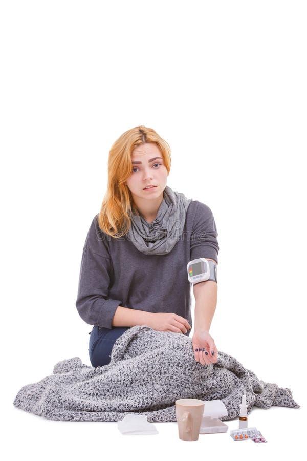 Больная девушка, сидит рядом с ее медицинами и давлением измерений с tonometer Изолировано на белизне стоковое фото rf