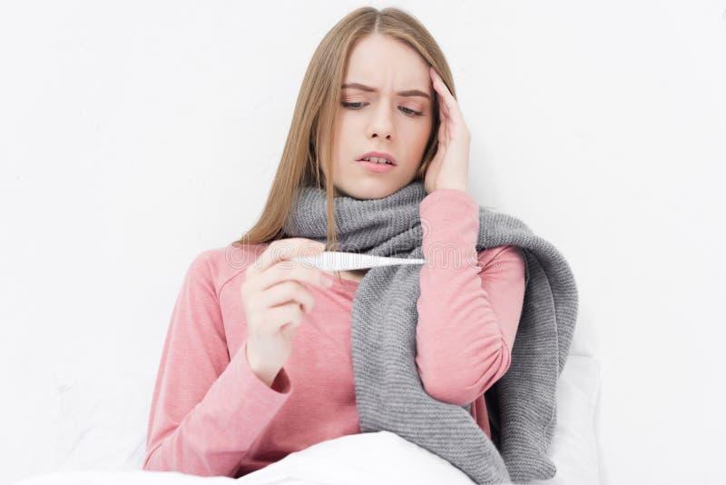 Больная девушка смотря на термометре стоковое фото rf