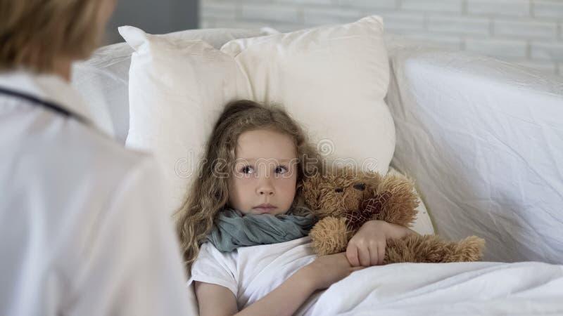 Больная девушка смотря педиатр в медицинской клинике, лежа в кровати, здравоохранение стоковое фото rf