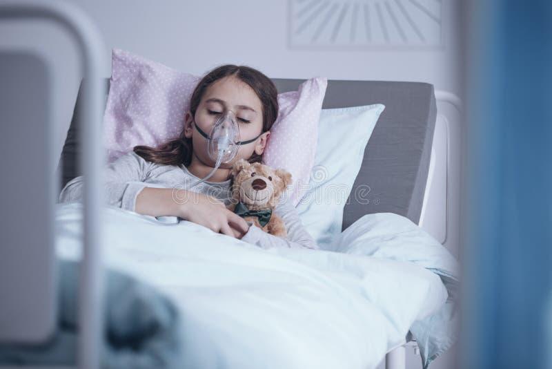 Больная девушка с кислородным изолирующим противогазом спать в больничной койке с игрушечным стоковая фотография rf