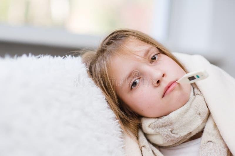 Больная девушка с термометром в рте смотря камеру стоковое фото rf
