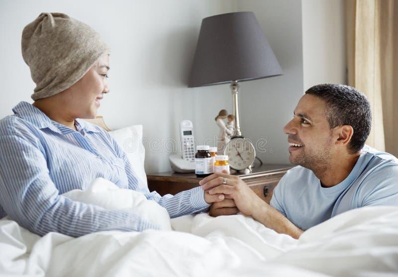 Больная женщина в кровати с ее партнером стоковые изображения