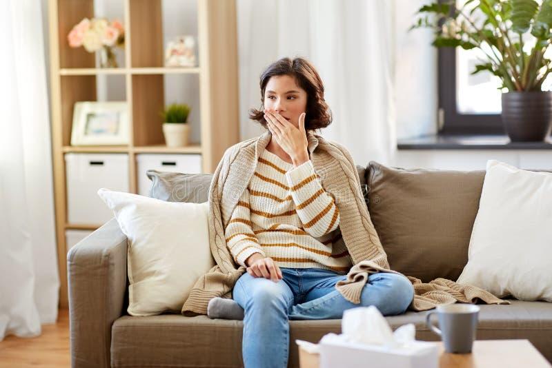 Больная женщина в одеяле кашляя дома стоковое изображение