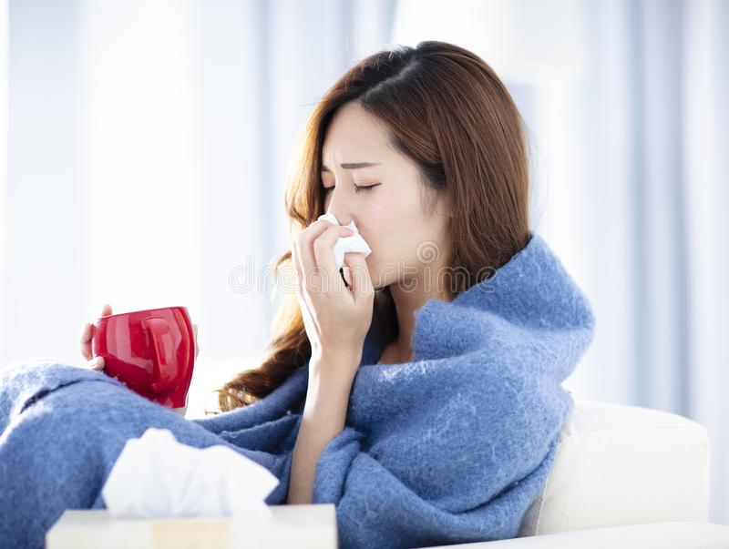 Больная женщина дуя ее нос пока сидящ на софе стоковое изображение rf