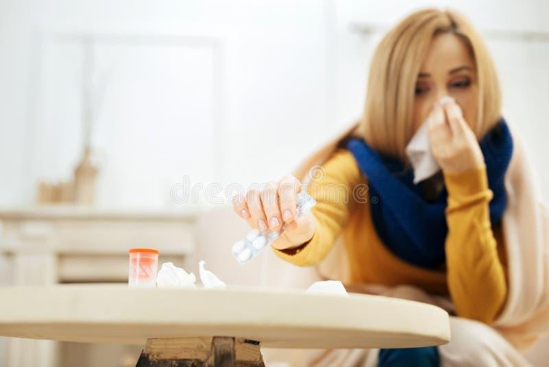 Больная женщина принимая пилюльки для того чтобы взять стоковое фото rf