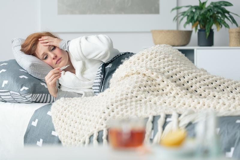 Больная женщина смотря термометр стоковое изображение rf