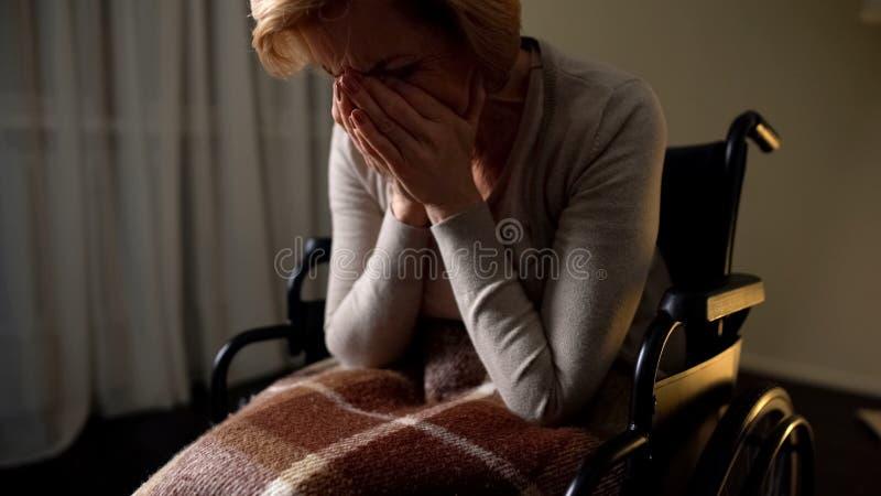 Больная кресло-коляска женщины чувствуя сиротливый и подавленный, безвыходность в доме престарелых стоковое изображение rf
