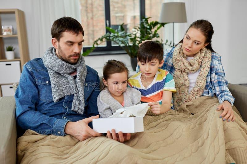 Больная семья с детьми имея грипп дома стоковая фотография