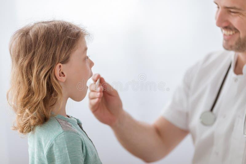 Больной мальчик с гриппом и педиатром проверяя его боль в горле стоковое фото rf