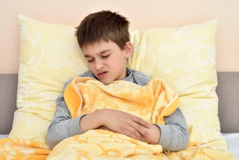Больной молодой мальчик сидя в кровати         6198 стоковое фото