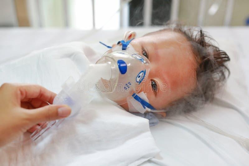 Больной применяться ребенка вдыхает лекарство маской вдыхания для того чтобы вылечить дыхательный синцитиальный вирус RSV на терп стоковые фото