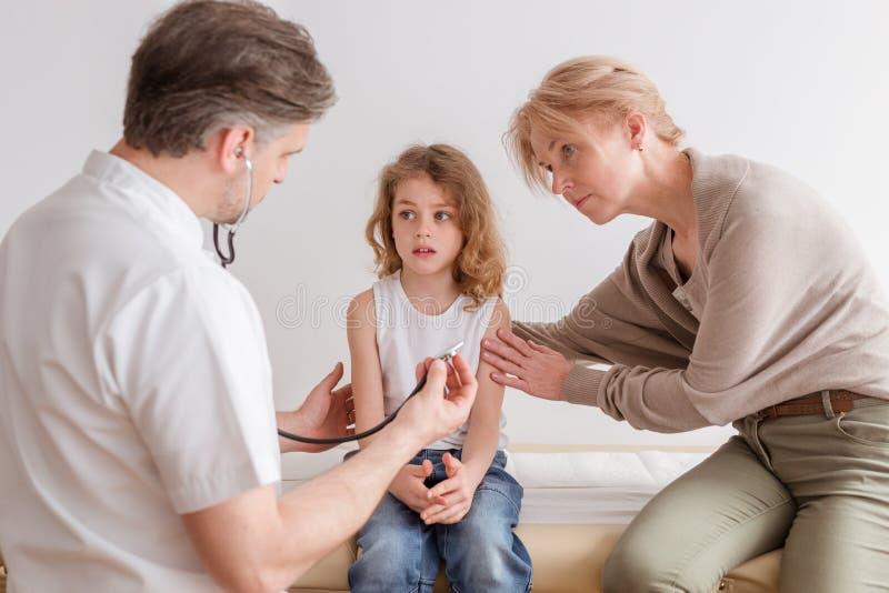Больной ребенок с симптомами пневмонии и профессиональный доктор в больнице стоковая фотография rf